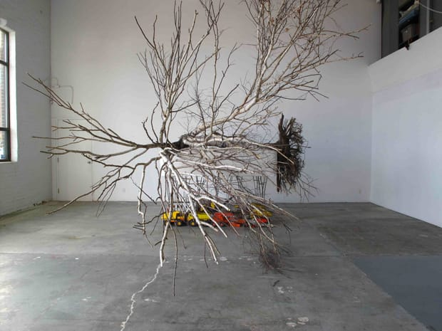 Max Dean, Tooth Fairy, 2010, mixed media, birch tree, mattress and box spring, steel trusses, strapping and seat belt buckle, metal cars and trucks, 3 x 3.7 x 4.9 m, collection of the artist.