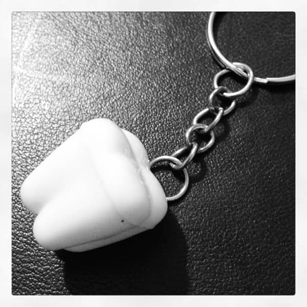 Black and white image of a tooth holder on a key ring