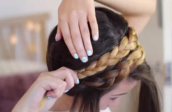 An image of one of the steps of how to do a milkmaid braid.