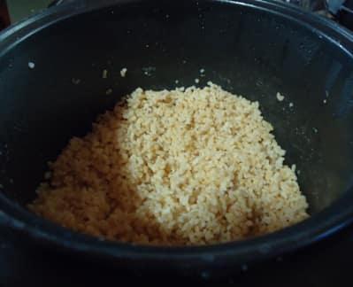Hot cooked brown rice in rice cooker.