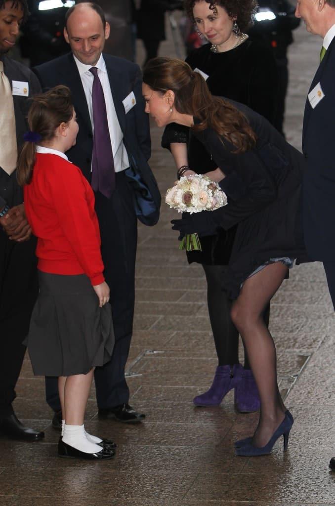 Kate Middleton greeting children when her navy blue skirt accidentally blows up