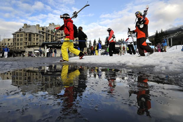 A man carries his skis as snow melts at the limit of the ski slopes in Whistler, BC, on Feb. 8, 2010.