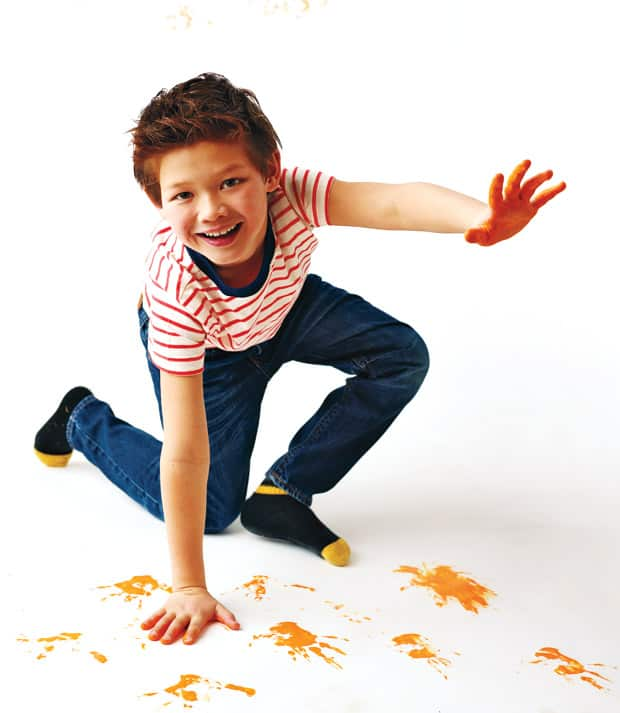 A young boy painting with his hands