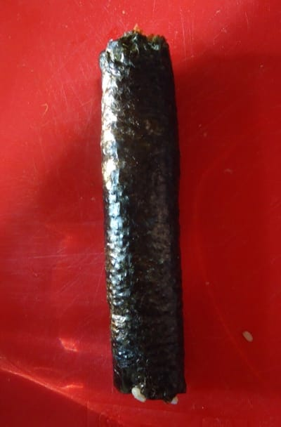 Roll it tightly using the sushi mat as a guide