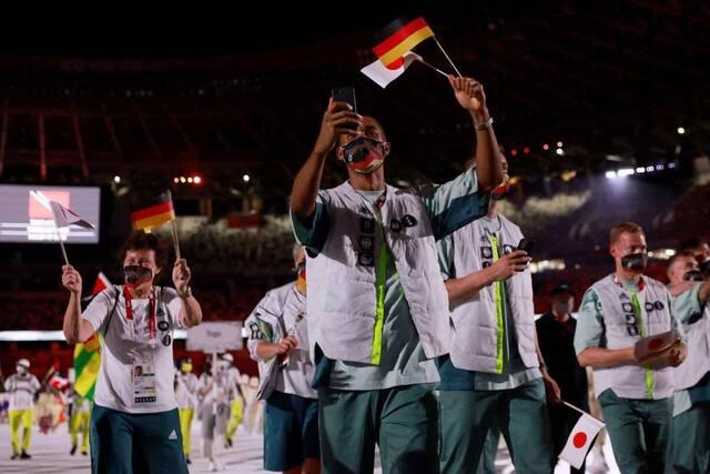 Un membre de la délégation allemande prend une selfie en défilant dans le Stade.