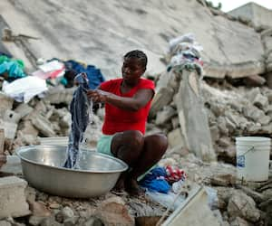Une femme nettoie ses vêtements à côté d'une maison détruite par l'important séisme du 12 janvier 2010.