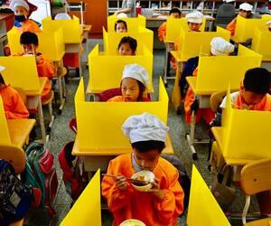 Des écoliers en pause repas à Taïwan, séparés par des paravents