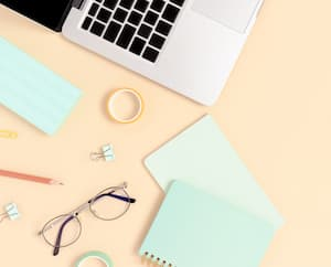 Top view of laptop, glasses and stationery on a yellow pastel background. Workspace concept banner with place for text.