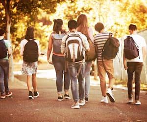 Rear view of school kids walking on road in campus