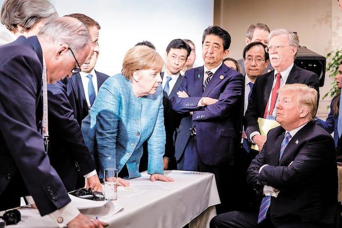 Donald Trump discutant avec la chancelière allemande Angela Merkel et entouré d'autres dirigeants du G7 lors d'une réunion du sommet du G7 à La Malbaie, en juin 2018.