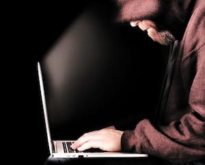 Hooded computer hacker using laptop
