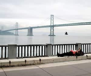 Un itinérant dort sur le trottoir près du Golden Gate de San Francisco.