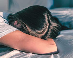 Depressed sleep deprived woman sick in bed late at night can't fall asleep on mattress. Winter seasonal affective disorder mental health illness woman crying alone at home banner panorama.
