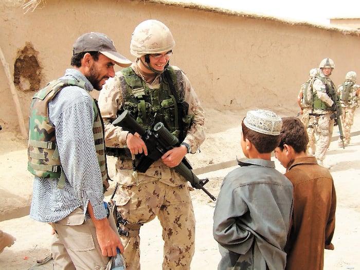 Simon Leduc en compagnie d'un interprète et des enfants lors d'un déploiement en Afghanistan.