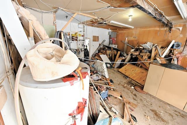 Le garage, qui a lui aussi  passé un mauvais quart  d'heure, est rempli de  décombres qui semblent  provenir de différentes  pièces de la maison.