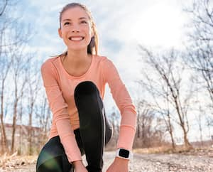 Autumn trail runner asian girl tying running shoes wearing sports smartwatch gadget gear. Female active athlete lacing shoe laces on forest path using smart watch heart rate fitness monitor.