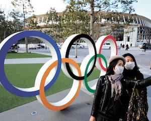 Des visiteurs se prennent en photo devant les anneaux olympiques installés à proximité du nouveau stade olympique de Tokyo, où la cérémonie d'ouverture des Jeux olympiques doit avoir lieu, le 24 juillet.