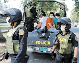 Des policiers ont embarqué dans un camion des citoyens de Lima, au Pérou, à un point de contrôle.
