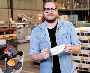 Le président des Industries Gould, Frederico Panetta espère aller de l'avant avec son projet d'agrandir son entrepôt d'Anjou ces prochaines semaines si l'industrie de la construction redémarre. On voit ici M. Panetta, dans son usine, montrant un des masques.