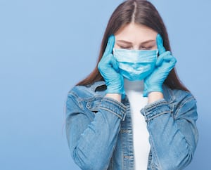 Close up portrait of woman wearing gloves and medical mask touching her head, posing isolated over blue studio background, having headache, touching temples. Corona virus, covid 19, healthcare concept