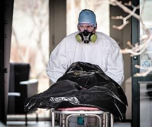 Un employé de la morgue quitte le CHSLD Herron hier avec une des personnes décédées.