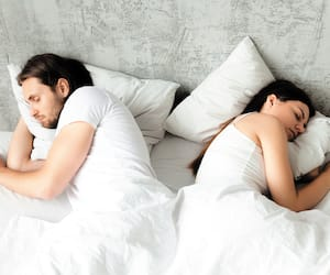 Unhappy indifferent couple sleeping separately back to back in b
