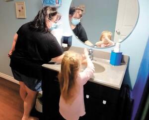 Annie Bossé aide la petite Kelly-Ann, 3 ans, à laver ses mains avant le dîner.
