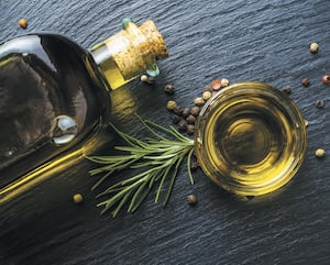 Extra virgin olive oil in a glass bottle, rosemary and peppercorns