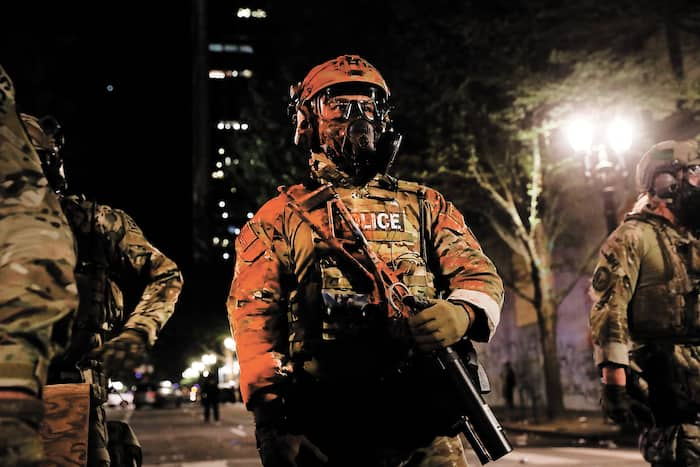 Des policiers fédéraux montent la garde devant la cour fédérale Mark O. Hatfield, à Portland, où des manifestants s'étaient donné rendez-vous dans la nuit de samedi à hier.