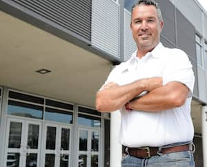 Éric Pouliot, le directeur de l'école secondaire Pointe-Lévy, située à Lévis. On le voit devant l'établissement, mardi. On y ouvrira notamment des locaux supplémentaires pour le dîner à la rentrée.