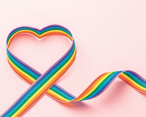 LGBT rainbow ribbon in the shape of heart. Pride symbol. Pink background. Copy space for text.