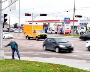 Sur un tronçon de sixkilomètres du boulevard Talbot, entre le boulevard du Royaume et la rue Jacques-Cartier, à Saguenay, on a dénombré 1496 accidents et 224blessés depuis2014. Daniel Simard, qu'on voit ici appuyer sur le bouton pour activer le feu pour piétons, affirme qu'il est difficile de traverser à cet endroit.