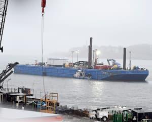 La barge de forage est amarrée dans le fleuve, près de la gare fluviale de Québec et des bâtiments de la Garde côtière canadienne.