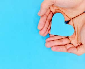 Cupped hands holding a blue heart in blue background. Charity, pure love, compassion and kindness concept. Top view.