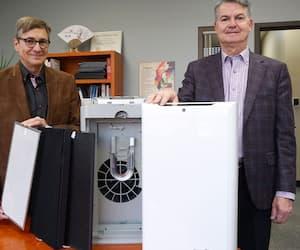 Normand Brais, vice-président fondateur et Jocelyn Dame, président de SANUVOX montrent les purificateurs d'air qui peuvent être installés en moins de deux minutes.