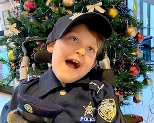 Noah Mercier, qui veut devenir policier, pose fièrement devant le sapin de Noël de la maison de soins palliatifs Le Phare.