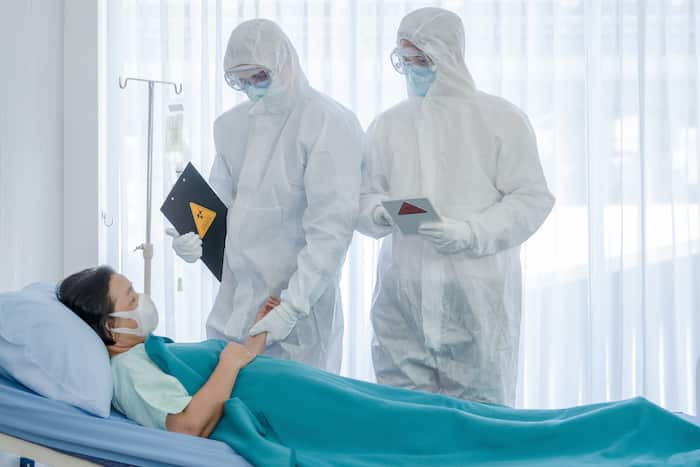 coronavirus covid 19 treatment background of coronavirus covid 19 patient on bed with doctors in PPE coverall suit in hospital negative pressure quarantine room, coronavirus covid 19 disease treatment