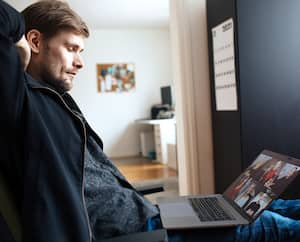 Tired man from work in home office. Fatigue from remote video call conference. Sleep deprivation, also known as insufficient sleep or sleeplessness. Businessman working on laptop during telework