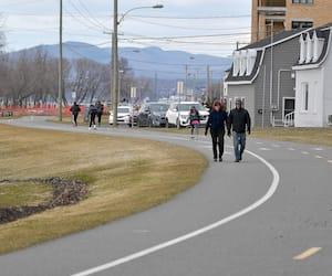 Des marcheurs et des planchistes ont profité du beau temps pour se promener en bordure de la rue Saint-Laurent, à Lévis, sur la Rive-Sud de Québec, où les nouveaux cas de COVID-19 ont explosé dans les derniers jours.