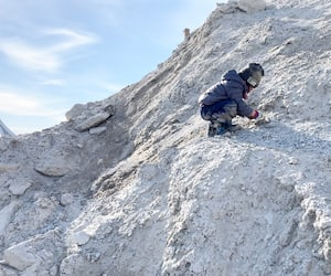 Le fils de notre chroniqueur est accroupi sur une «montagne» sur un terrain vague.
