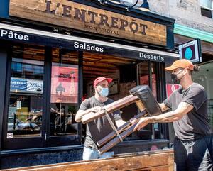 Mac Charette (à gauche) et Nicolas Brassard, du restaurant L'Entrepôt de l'avenue Mont-Royal, à Montréal, montent leur terrasse en vue de l'ouverture, vendredi.