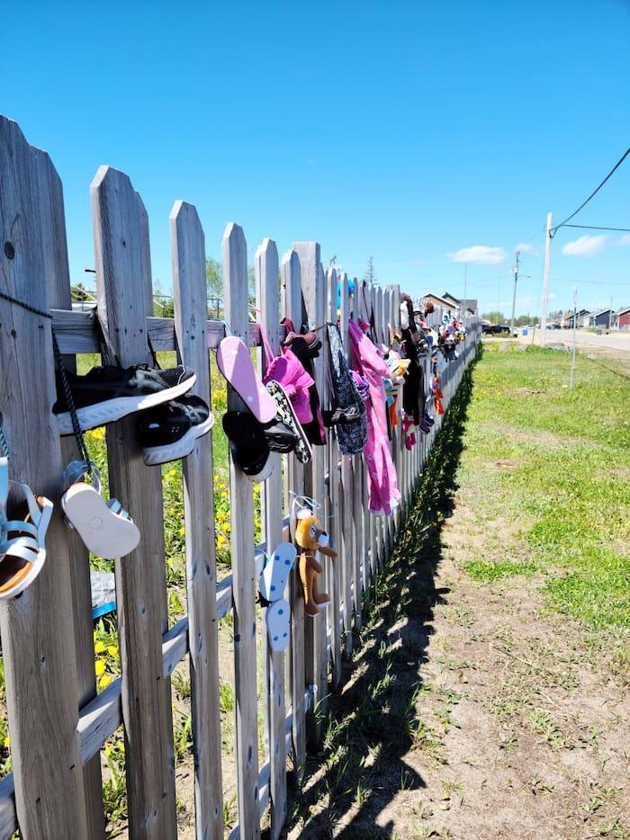 Objets d'enfants accrochés à la clôture de l'ancien pensionnat de Maliotenam, à Sept-Îles.
