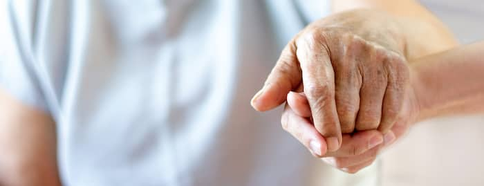 Caregiver, carer hand holding elder hand in hospice care background. Philanthropy kindness to disabled old people concept.Happy mother's day.