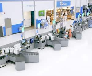 Les consommateurs doivent de plus en plus utiliser les caisses en libre-service et emballer leur marchandise, comme on le voit ici dans un Walmart.