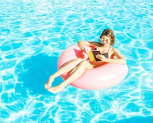 Beautiful happy woman reading a book with inflatable ring relaxing in blue swimming pool