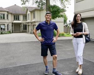L'homme d'affaires Bob Liu et la courtière immobilière Jasmine Zou devant la demeure de M.Liu, à Beaconsfield.