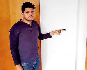Ripon Ahmed devant deux trous qu'ont percé les policiers dans le mur de sa chambre pour extirper les projectiles.