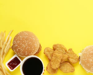 Different fast food on yellow background, flat lay. Space for text