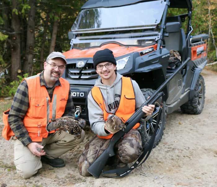 Le directeur de la réserve faunique de Mastigouche, Éric Harnois (à gauche), a pris la pause avec son fils Jacob et quelques-unes des gélinottes que nous avons récoltées lors de notre sortie de chasse en quad.