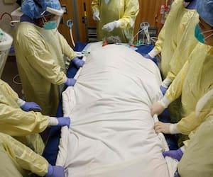 L'anesthésiste, le Dr Jason Cyr, ajuste les tubes du ventilateur alors que les travailleurs de la santé tournent un patient souffrant de coronavirus de sa position couchée à l'unité de soins intensifs de l'hôpital Humber River, à Toronto, Ontario, le 28 avril, 2021.